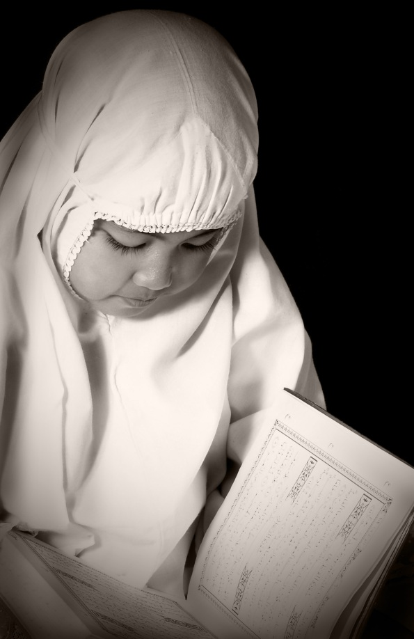 A small girl reading holy quran